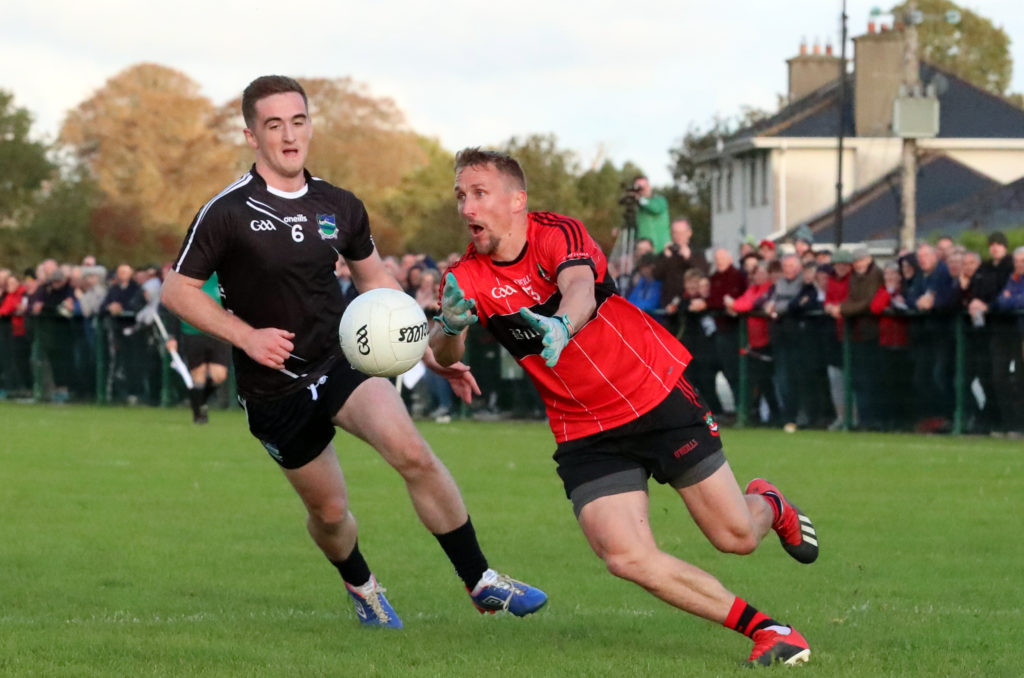 Mikey Lyons get his pass away despite the attention of Stephen Brosnan in the 2019 Limerick SFC semi-final between Adare and Newcastle West. CREDIT: Sport Action Photography